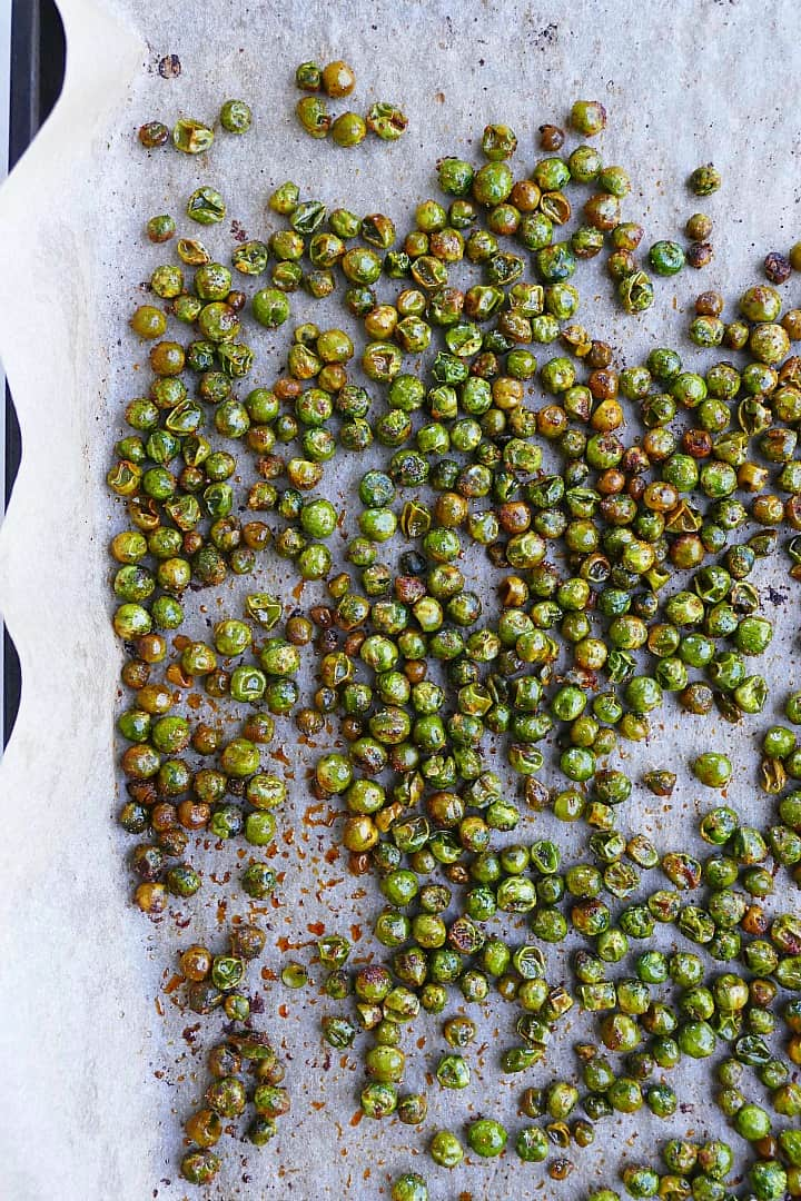 roasted peas spread out on a baking sheet lined with parchment paper