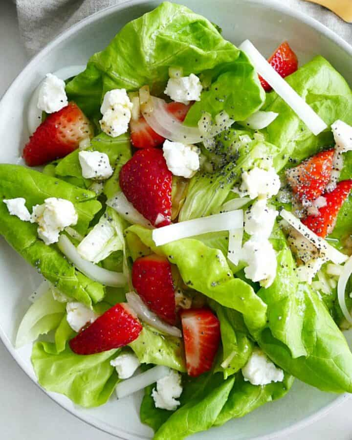 square image of strawberry goat cheese salad on a white plate on a counter