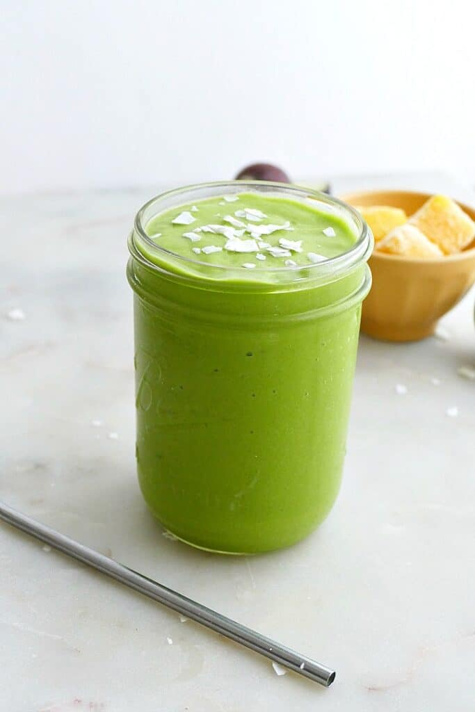 photography of a green smoothie in a glass jar with mango in the background