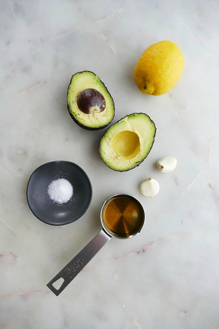 avocado, lemon, garlic cloves, salt, and olive oil on a white counter