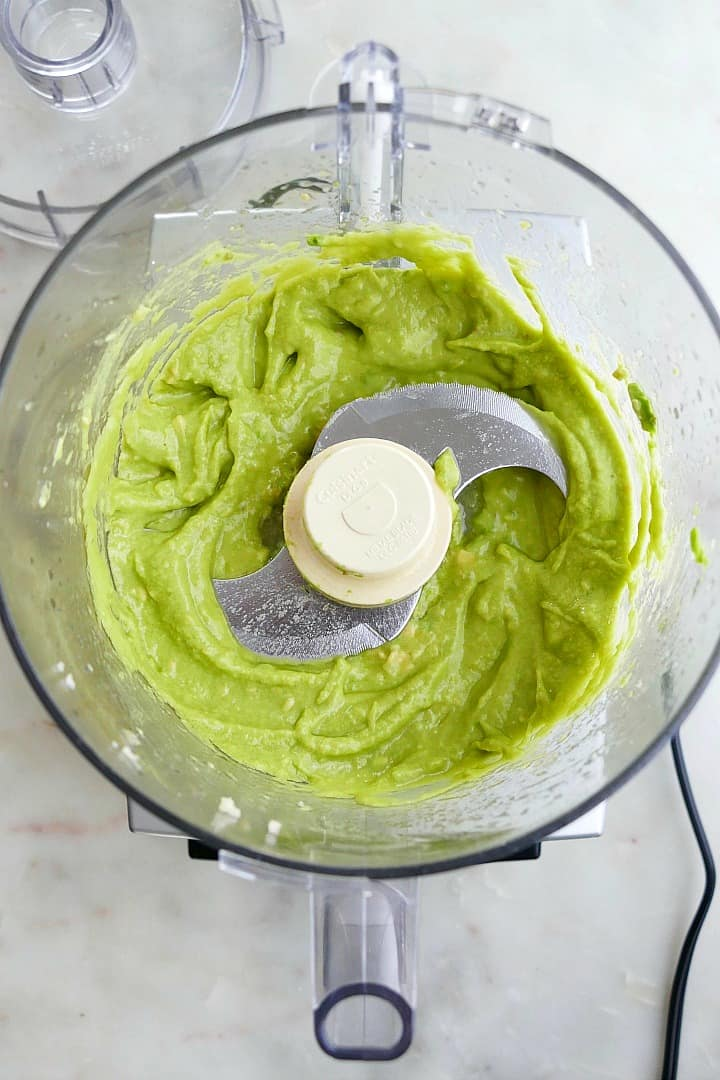 whipped avocado spread in a food processor on a white counter