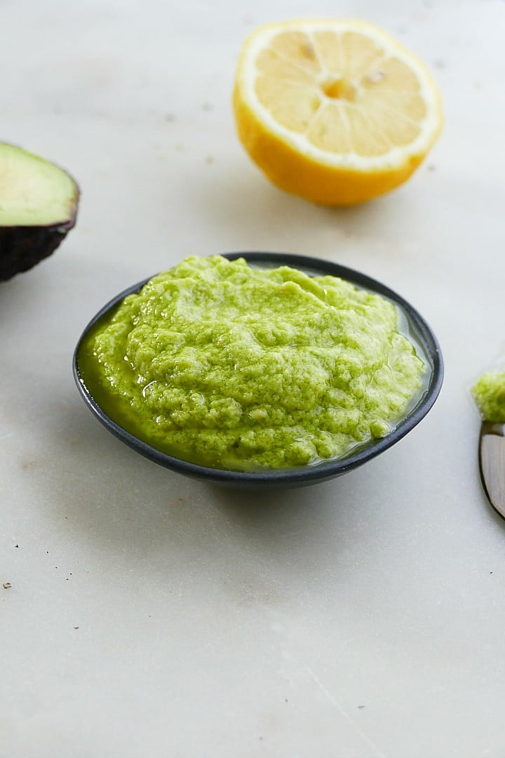 side view of garlic avocado spread in a black bowl with a lemon behind it
