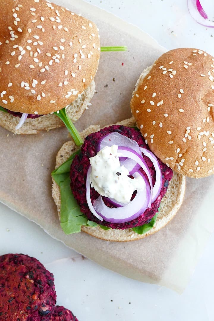 black bean beet burger on a whole wheat seeded bun with onion and mayo