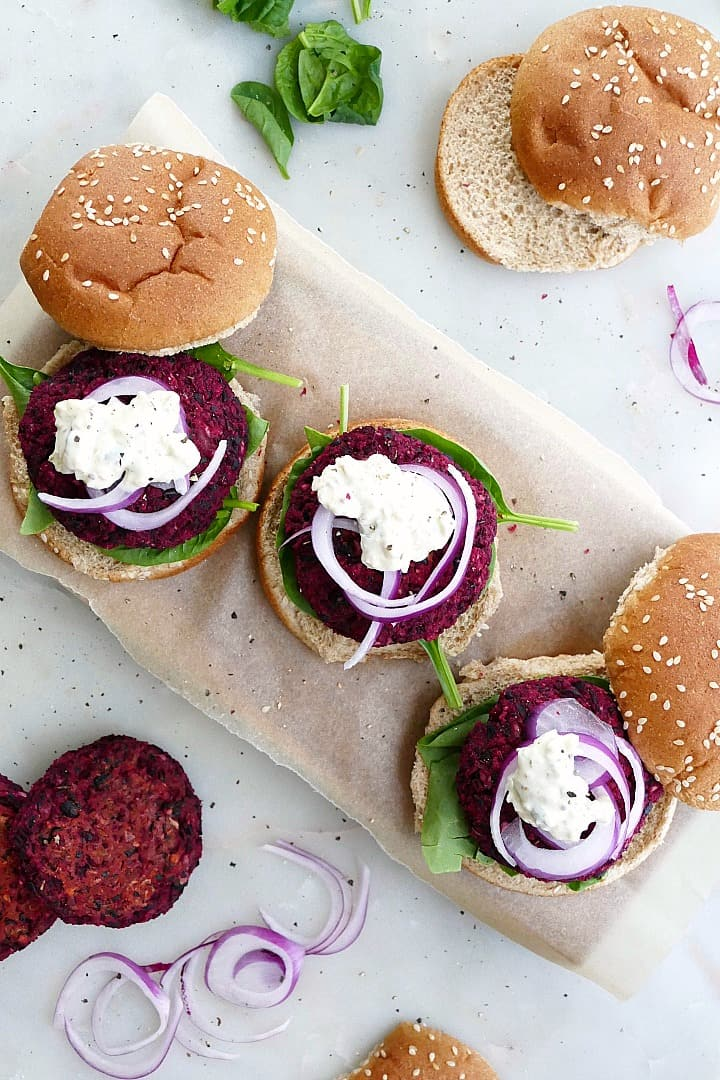 three beet black bean burgers on a piece of parchment paper with buns and toppings
