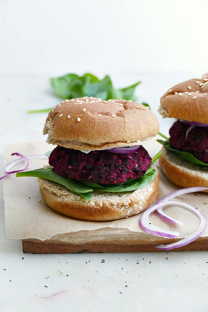 black bean beet burger on a seeded whole wheat bun with lettuce, onion, and mayo