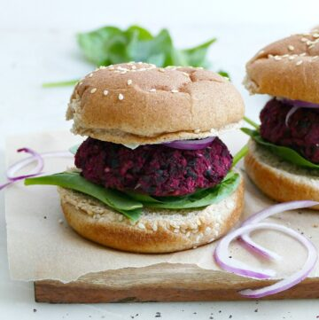 square image of a black bean beet burger on a whole wheat bun next to some sliced onions