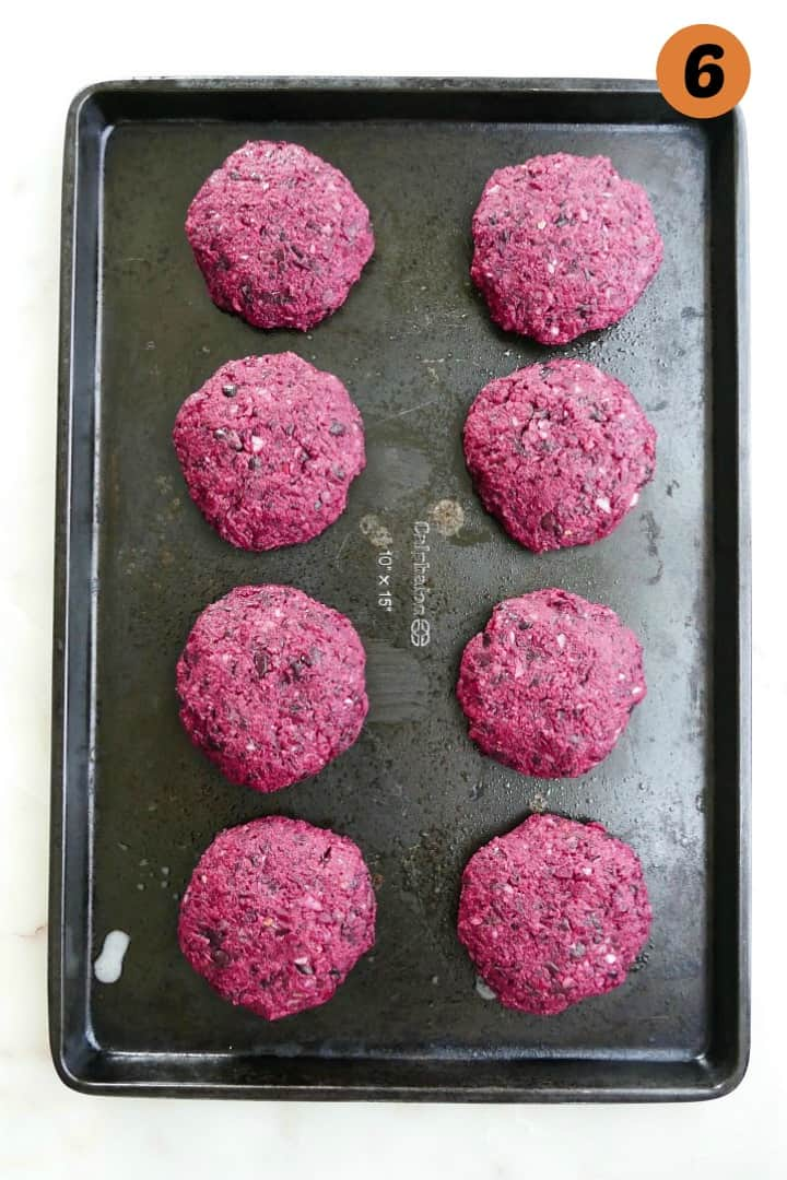 8 black bean beet burger patties on a baking sheet on a counter