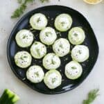 cucumber canapes on a black plate on a counter surrounded by dill