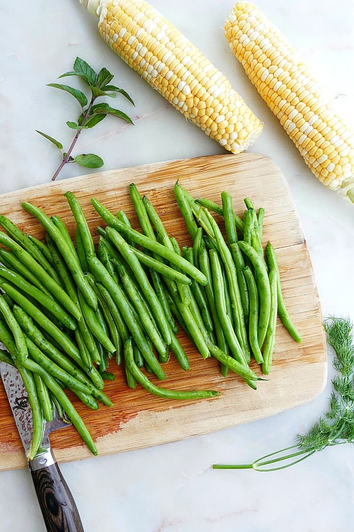 green beans on a bamboo cutting board next to 2 ears of corn