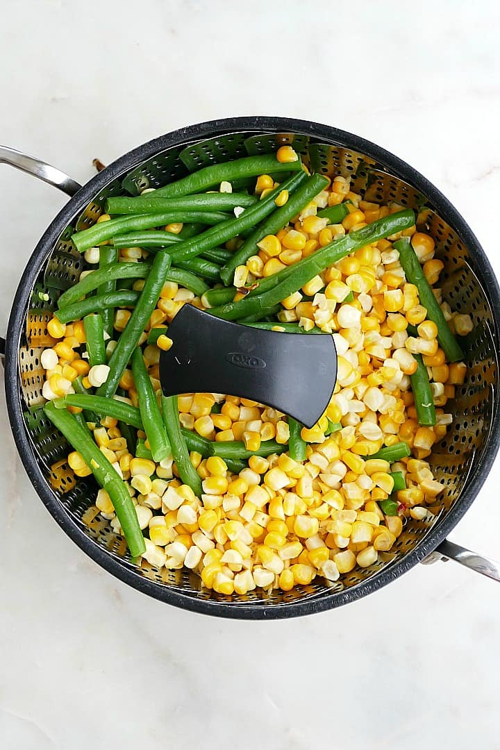 corn kernels and trimmed green beans in a veggie steamer basket in a pot