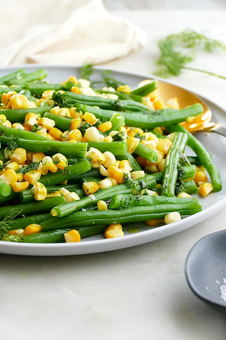 side angle of green beans and corn with fresh herbs and a gold spoon