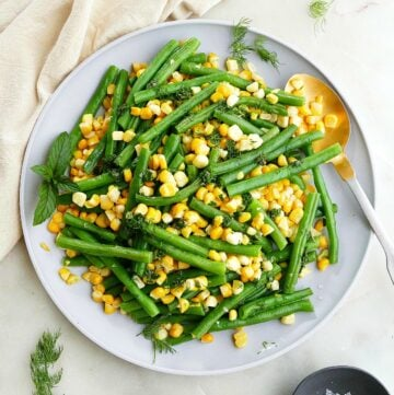 square image of green beans and corn on a gray plate with gold spoon
