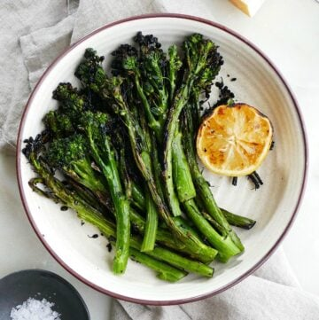 square image of grilled broccolini and lemon on top of a gray napkin