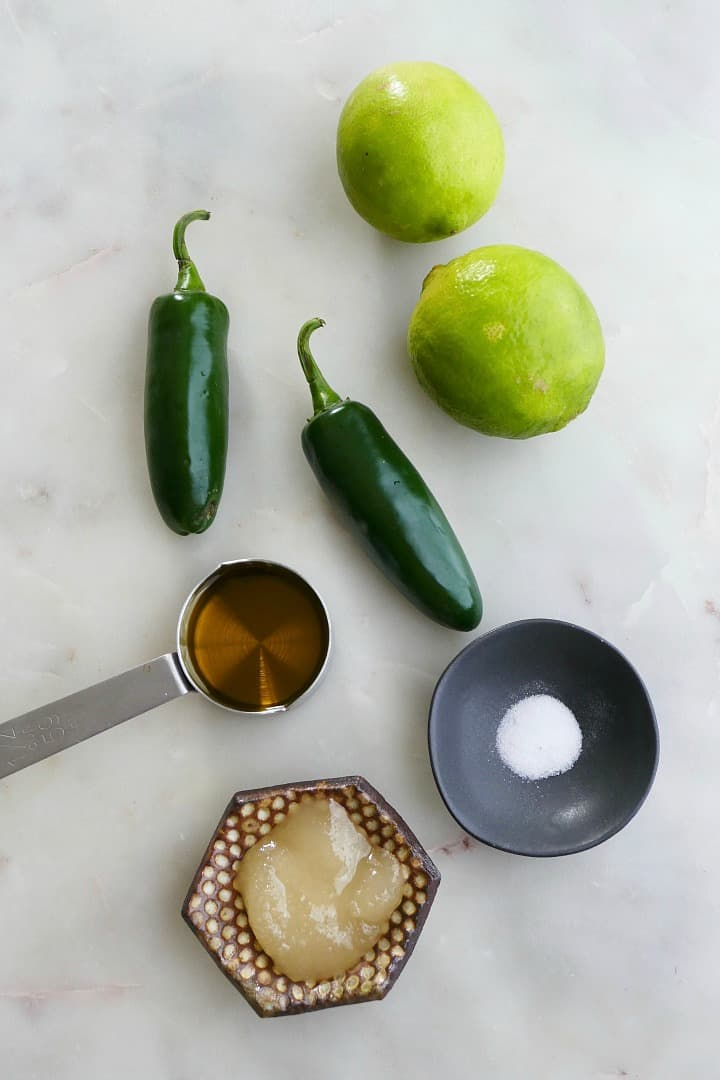 jalapenos, limes, honey, olive oil, and salt on a white counter