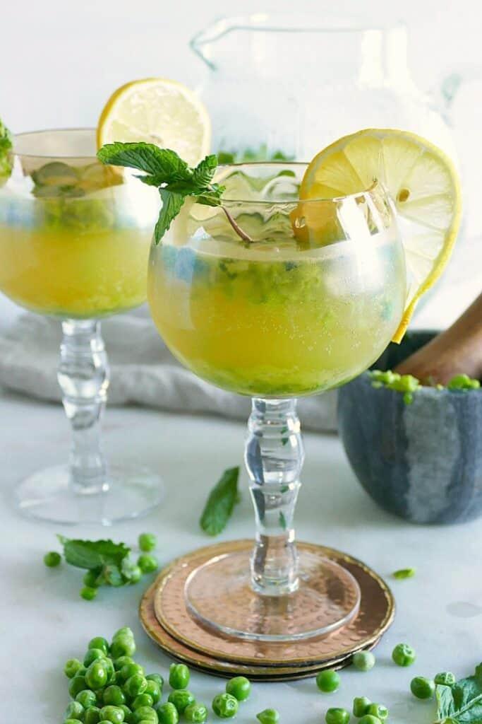 two long stem glasses with kombucha mocktails garnished with lemon slices