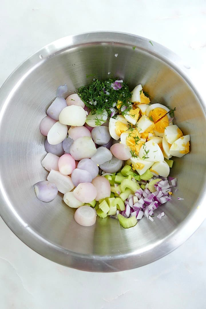 ingredients for radish potato salad in a silver mixing bowl on a counter
