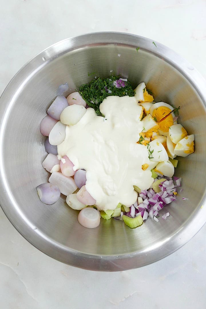 recipe ingredients in a silver mixing bowl smothered with a yogurt dressing
