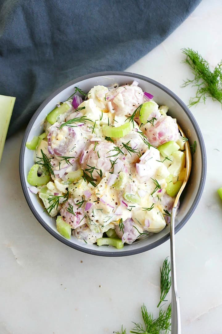 radish potato salad topped with fresh dill in a gray bowl with a spoon