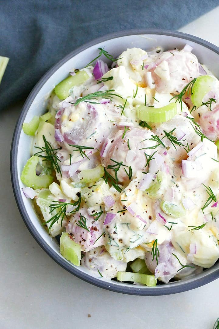 close up of radish potato salad with fresh dill in a bowl on a counter