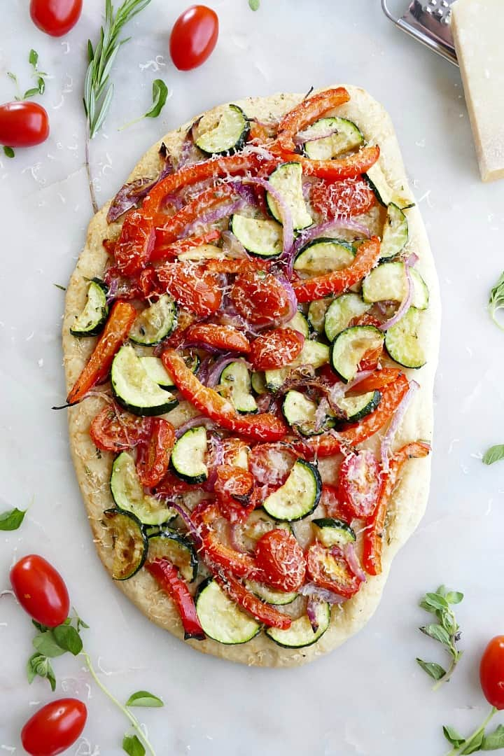 mediterranean roasted veggie flatbread on a white counter surrounded by ingredients and herbs