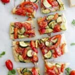 flatbread topped with tomatoes and summer veggies sliced into 8 pieces