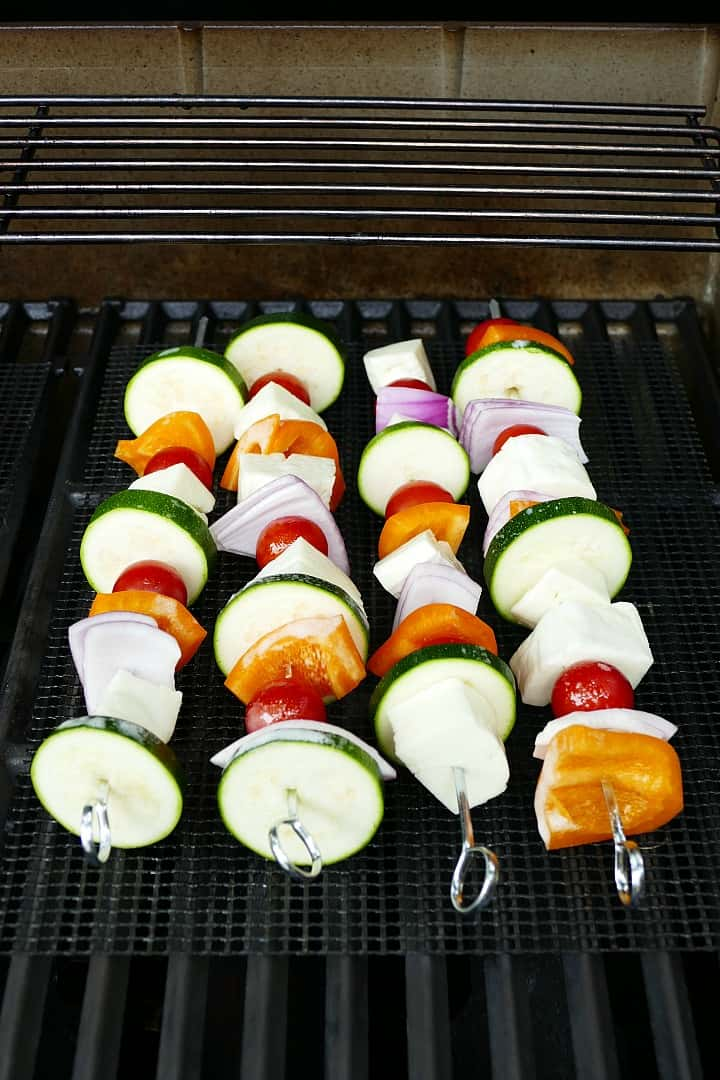 metal skewers with vegetables and halloumi on top of a mesh grill mat on a grill