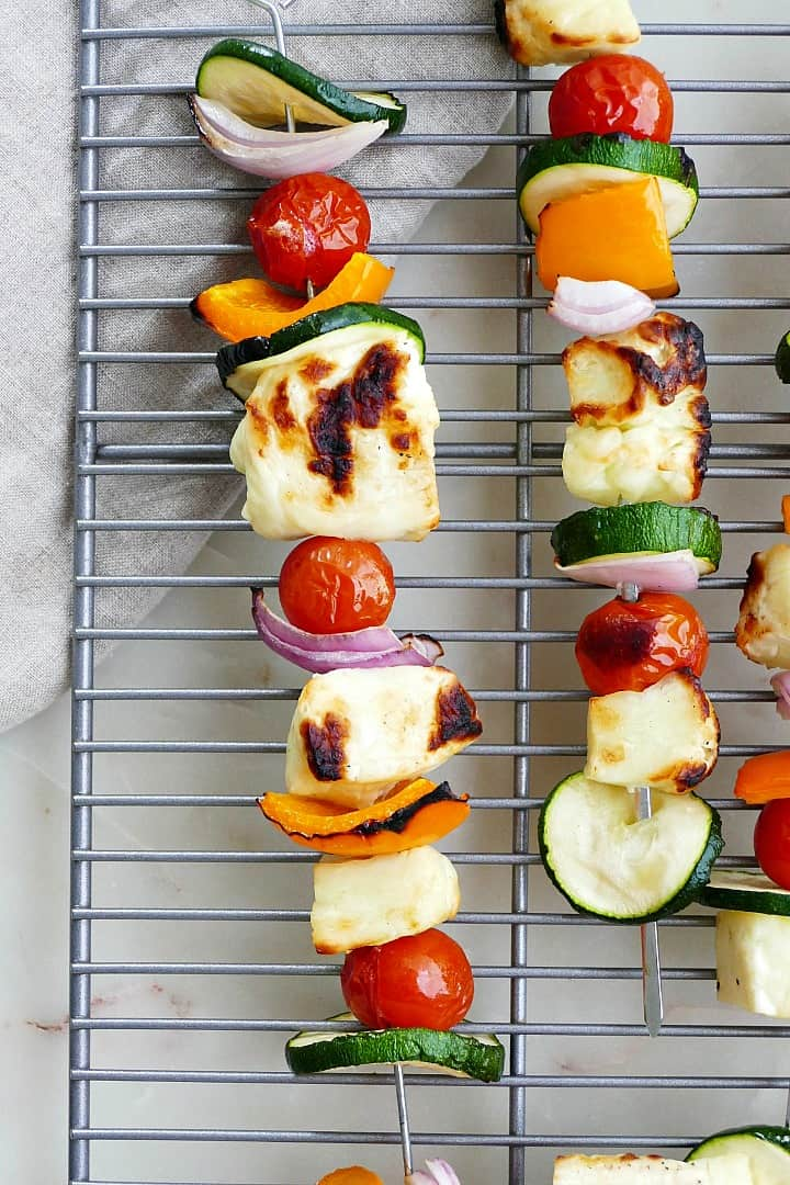 close shot of vegetable and halloumi skewers on top of a cooling rack