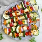 six grilled veggie and halloumi skewers on a serving plate on a counter