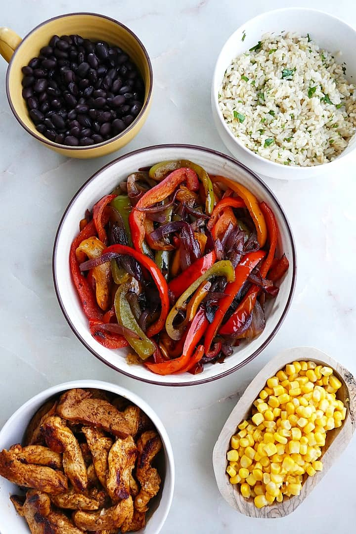 black beans, rice, fajita veggies, corn, and chicken in bowls on a counter