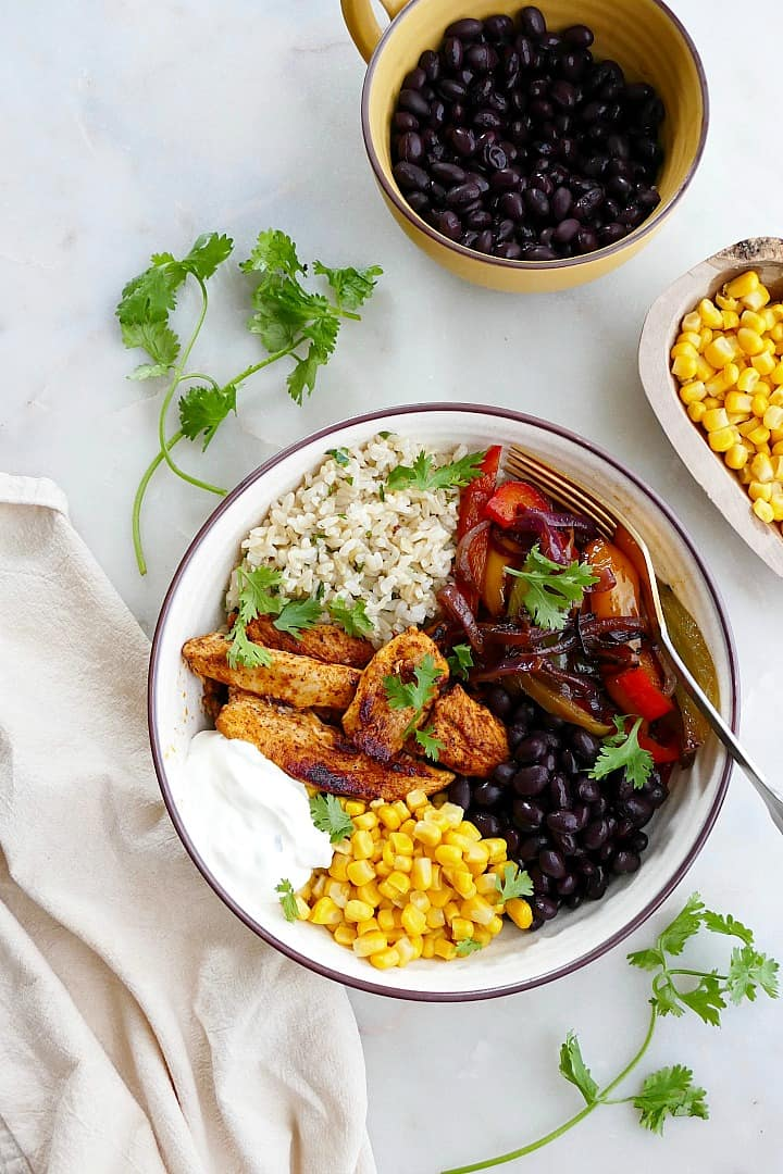 chicken fajita bowl with toppings on a counter next to ingredients and a napkin