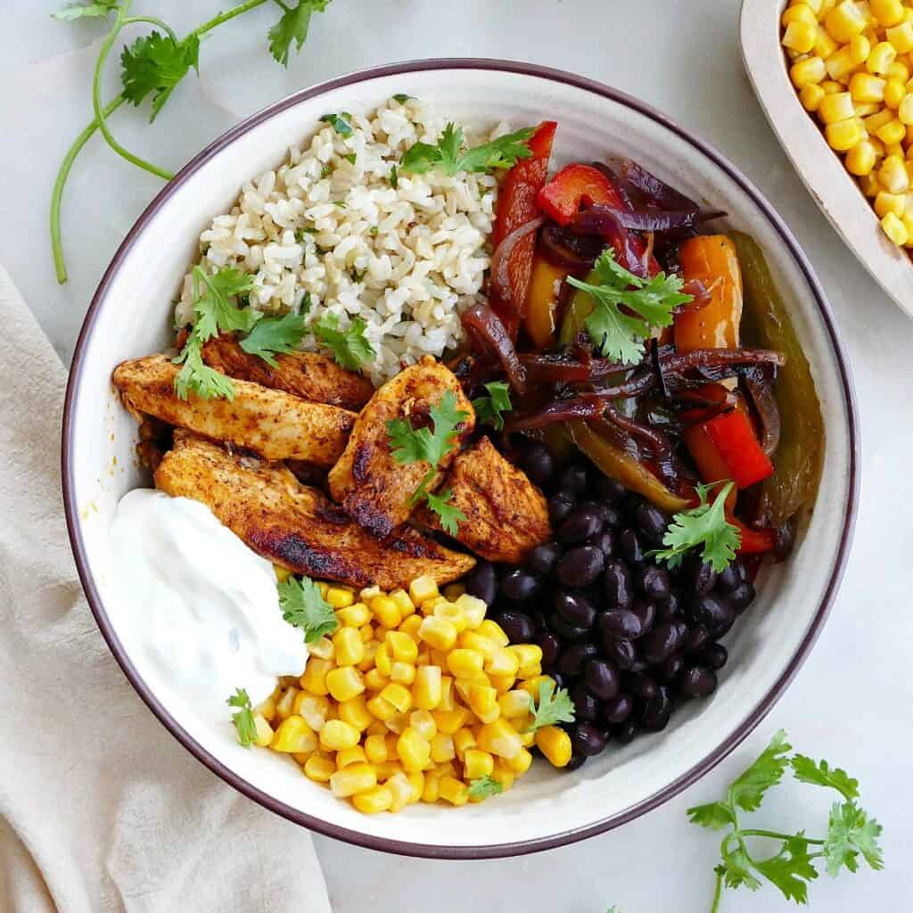 square image of chicken fajita bowl with toppings on a counter