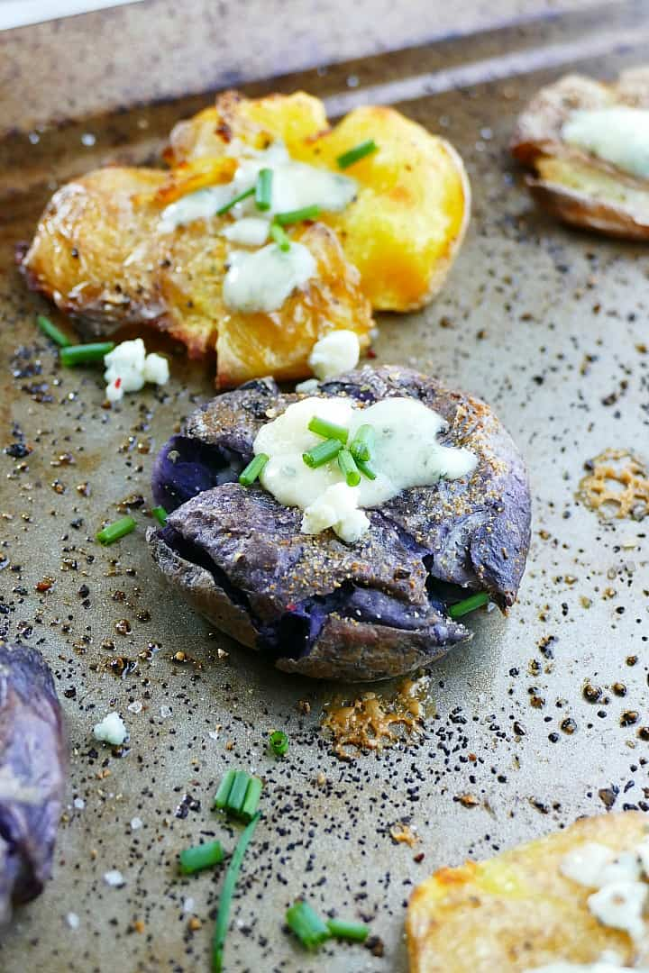 crispy smashed potatoes with blue cheese and chives on a baking sheet