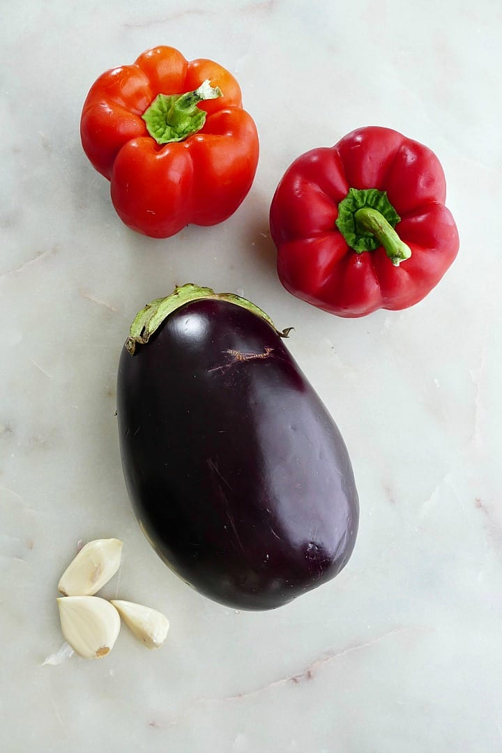 two red peppers, one large eggplant, and three garlic cloves spread out on a counter