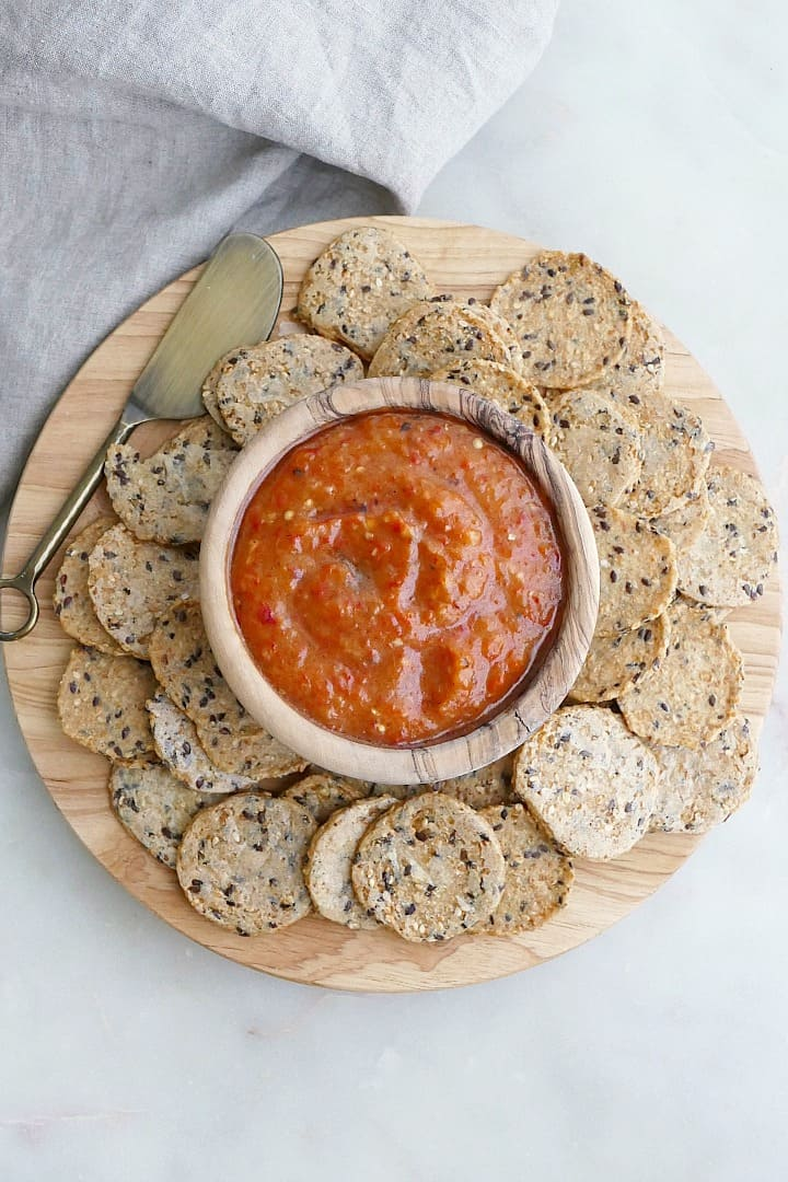 bowl of dip surrounded by seed crackers on a circular wooden serving board