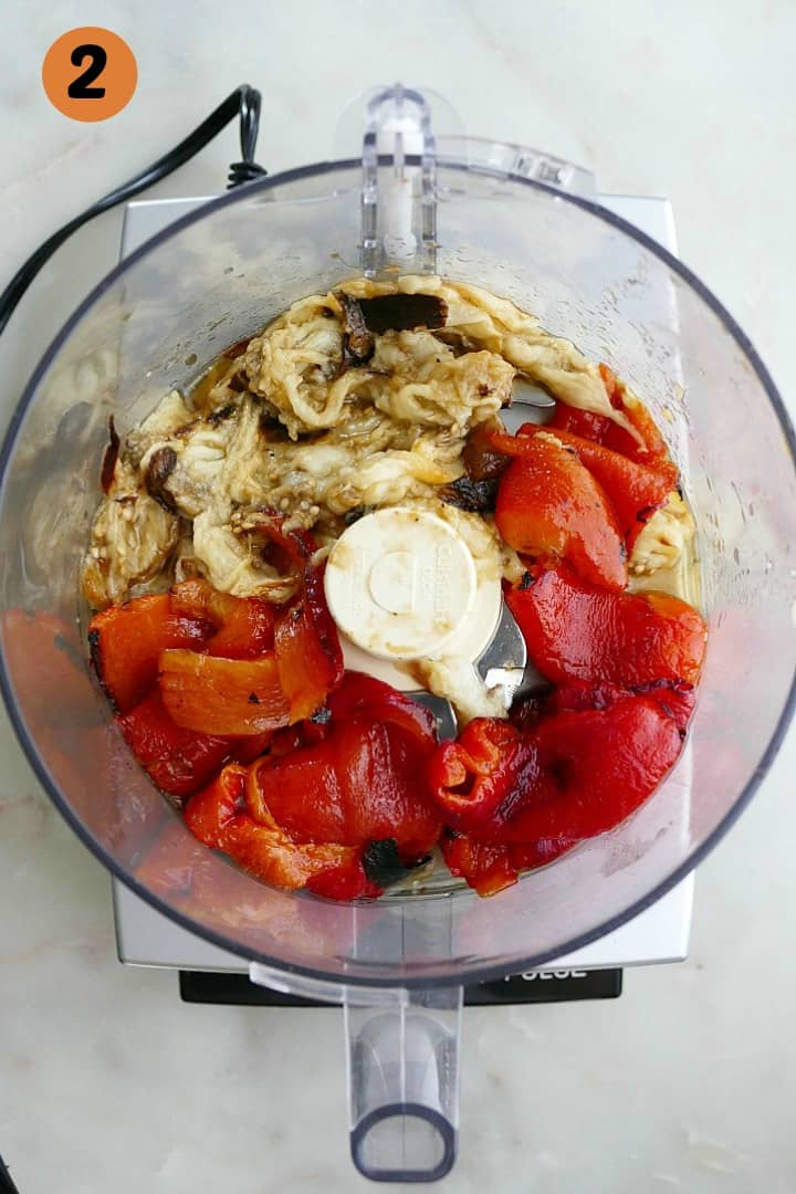 roasted eggplant and red peppers in a food processor with the number 2 in the corner