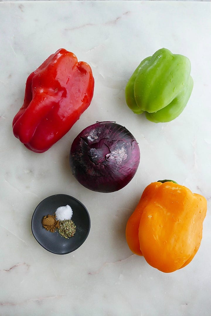 three bell peppers, a red onion, and a dish with seasonings on a counter