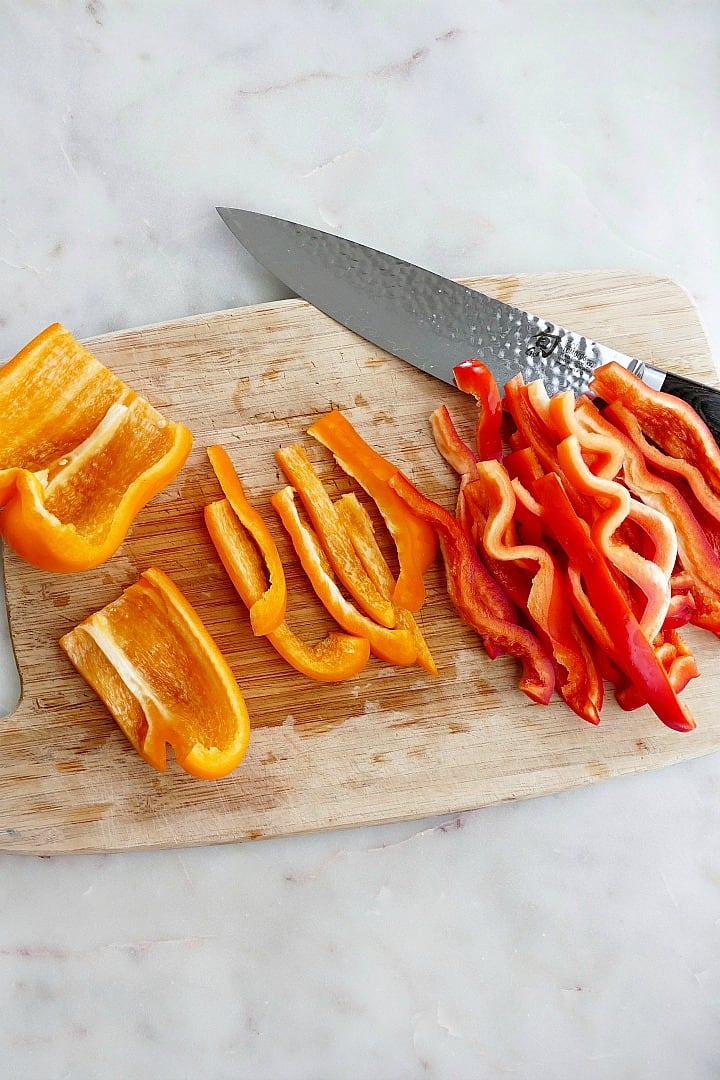thinly sliced red and orange bell peppers on a cutting board with a chef's knife