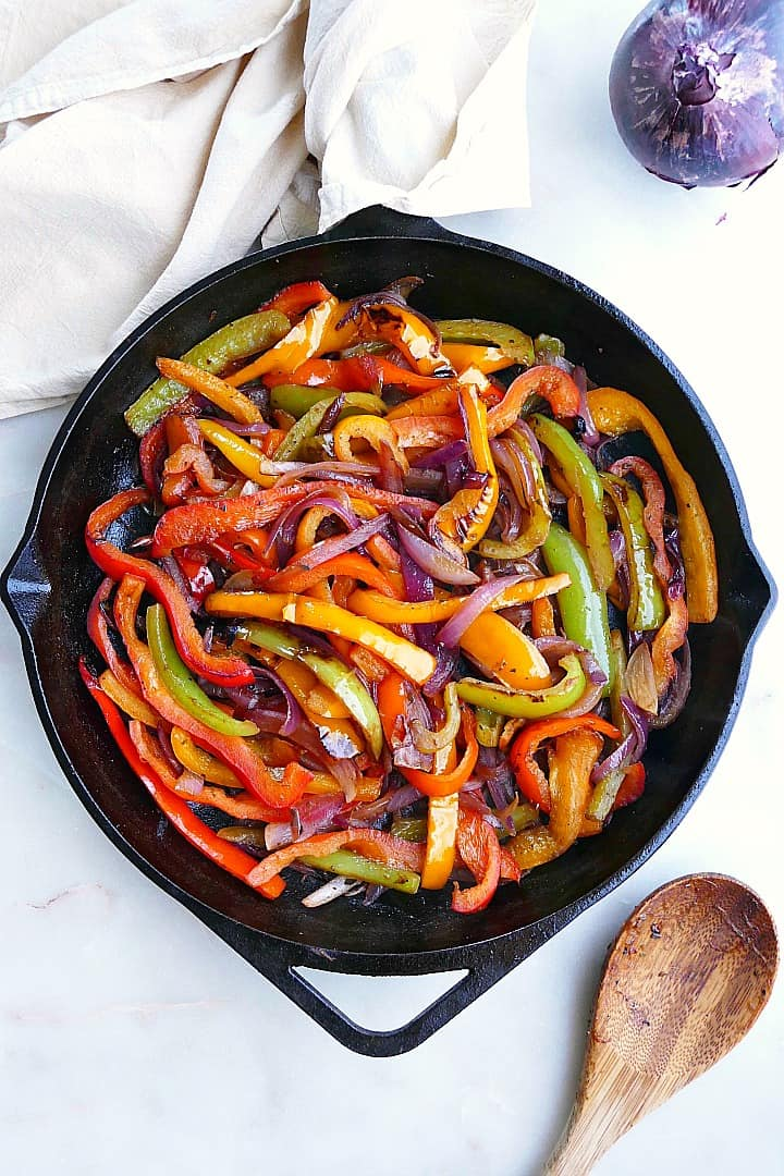 cooked fajita veggies in a cast iron skillet next to a spoon and napkin