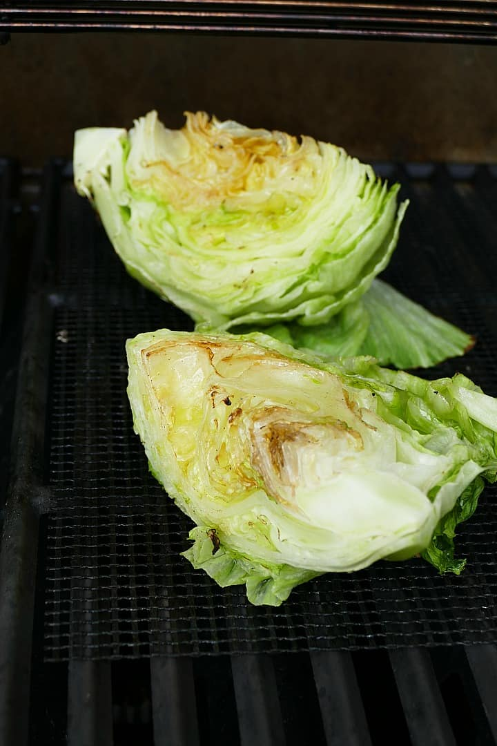 two iceberg lettuce wedges on a mesh grill mat on a grill