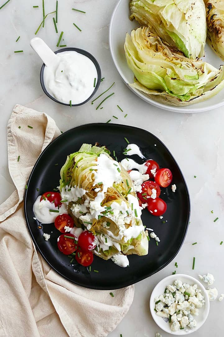 grilled wedge salad with blue cheese dressing on a plate on a counter