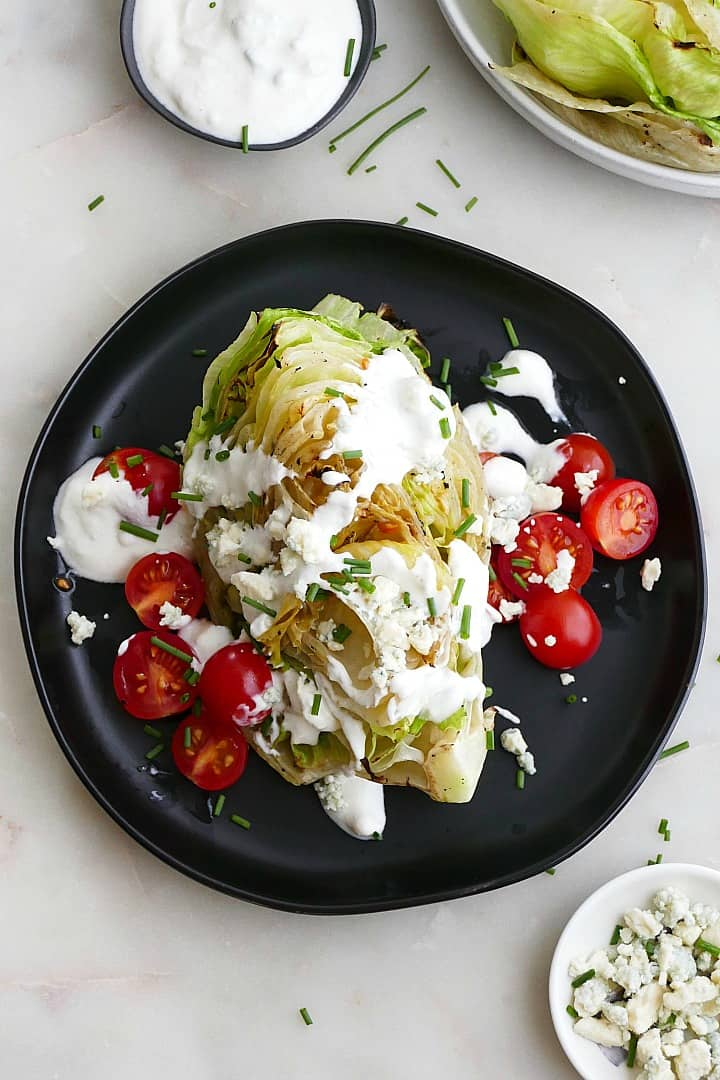 wedge salad with blue cheese dressing and cherry tomatoes on a black plate