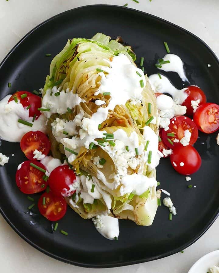 square image of grilled wedge salad with tomatoes and dressing on a plate