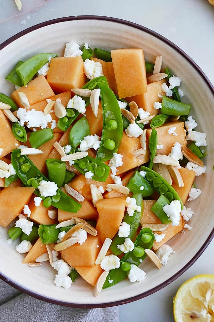 sugar snap pea, cantaloupe, slivered almonds, and goat cheese in a bowl on a counter