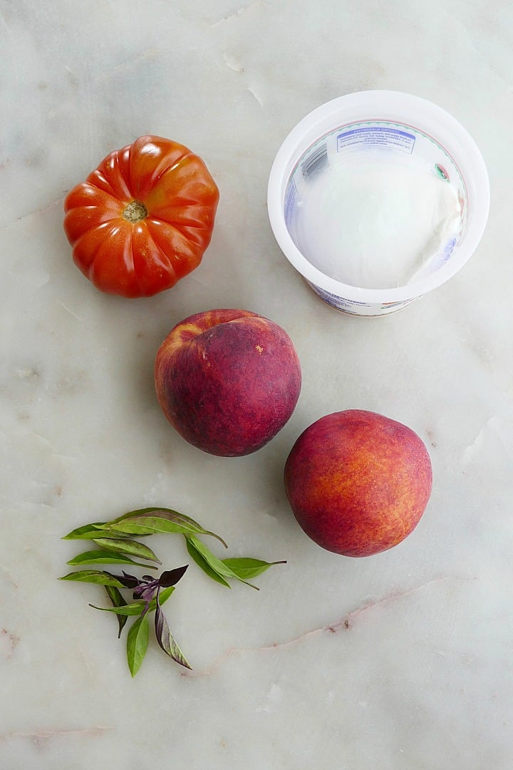 heirloom tomato, two peaches, ball of mozzarella, and basil leaves next to each other on a counter