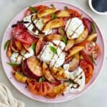 peach caprese salad drizzled with balsamic and garnished with basil on a platter