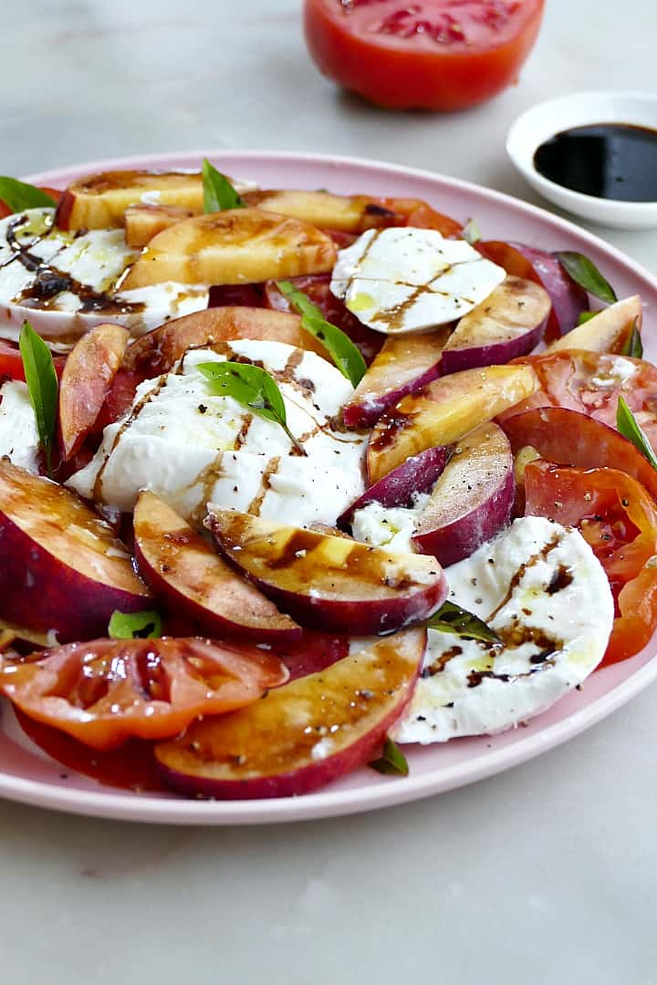 peach and tomato salad with mozzarella, balsamic, and basil on a platter