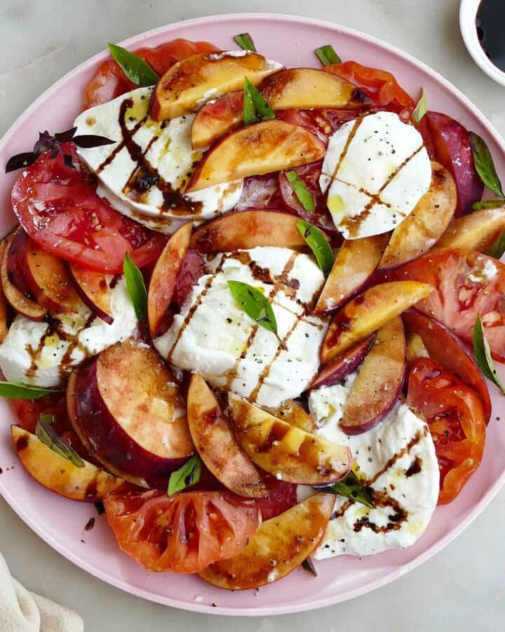square image of peach caprese salad garnished with basil and balsamic on a platter