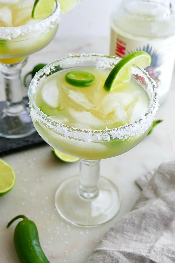 pineapple jalapeno margarita garnished with a salt rim and lime wedges on a counter