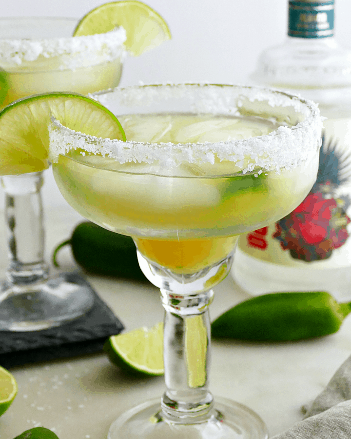 pineapple jalapeno margaritas on a counter garnished with salt rims and lime