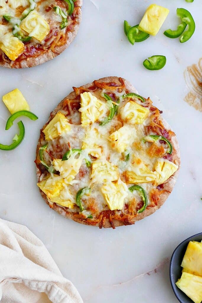 pineapple jalapeno pizza on a counter next to ingredients and a napkin